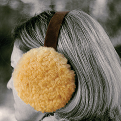 woman wearing a pair of lambswool ear muffs side view.