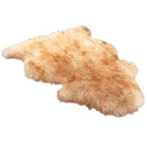 a long-wool sheepskin rug, tan/brown in color.