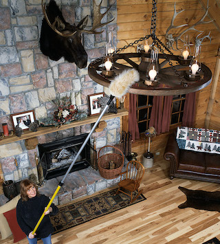 woman dusting a chandelier in an upscale lodge