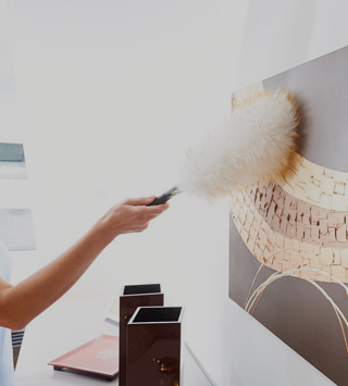 woman dusting a painting with a wool duster